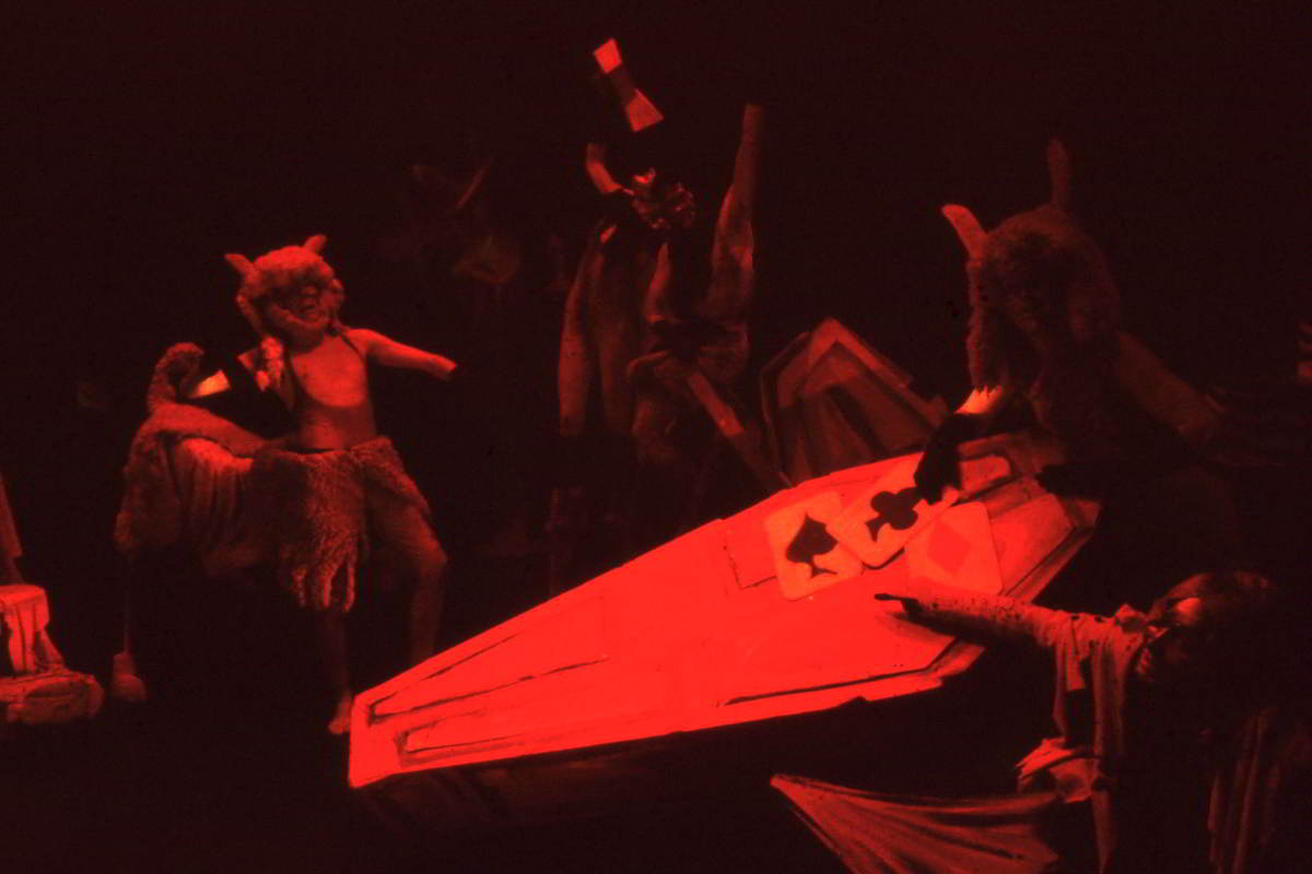 Handspan Theatre Four Little Girls Demons and satyrs play a card game on a coffin