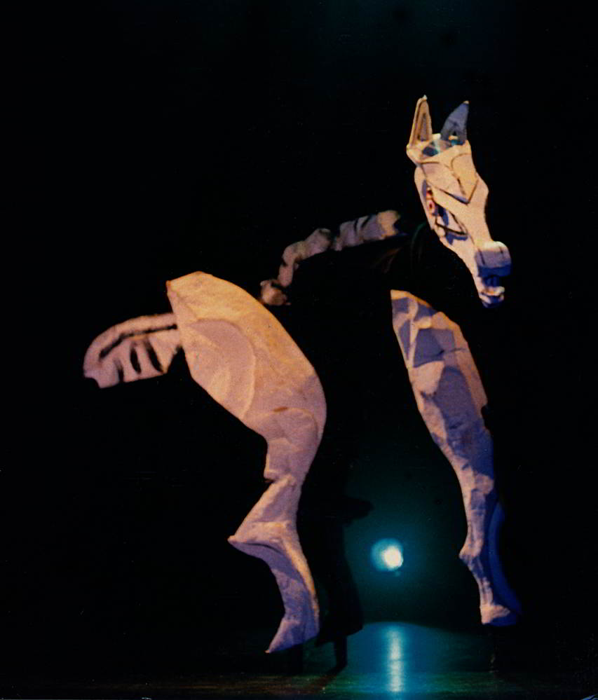 Puppeteer walks on two pairs of stilts costumed as giant horse