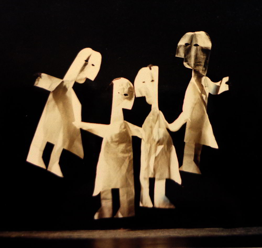 Four life-size dolls against a black background