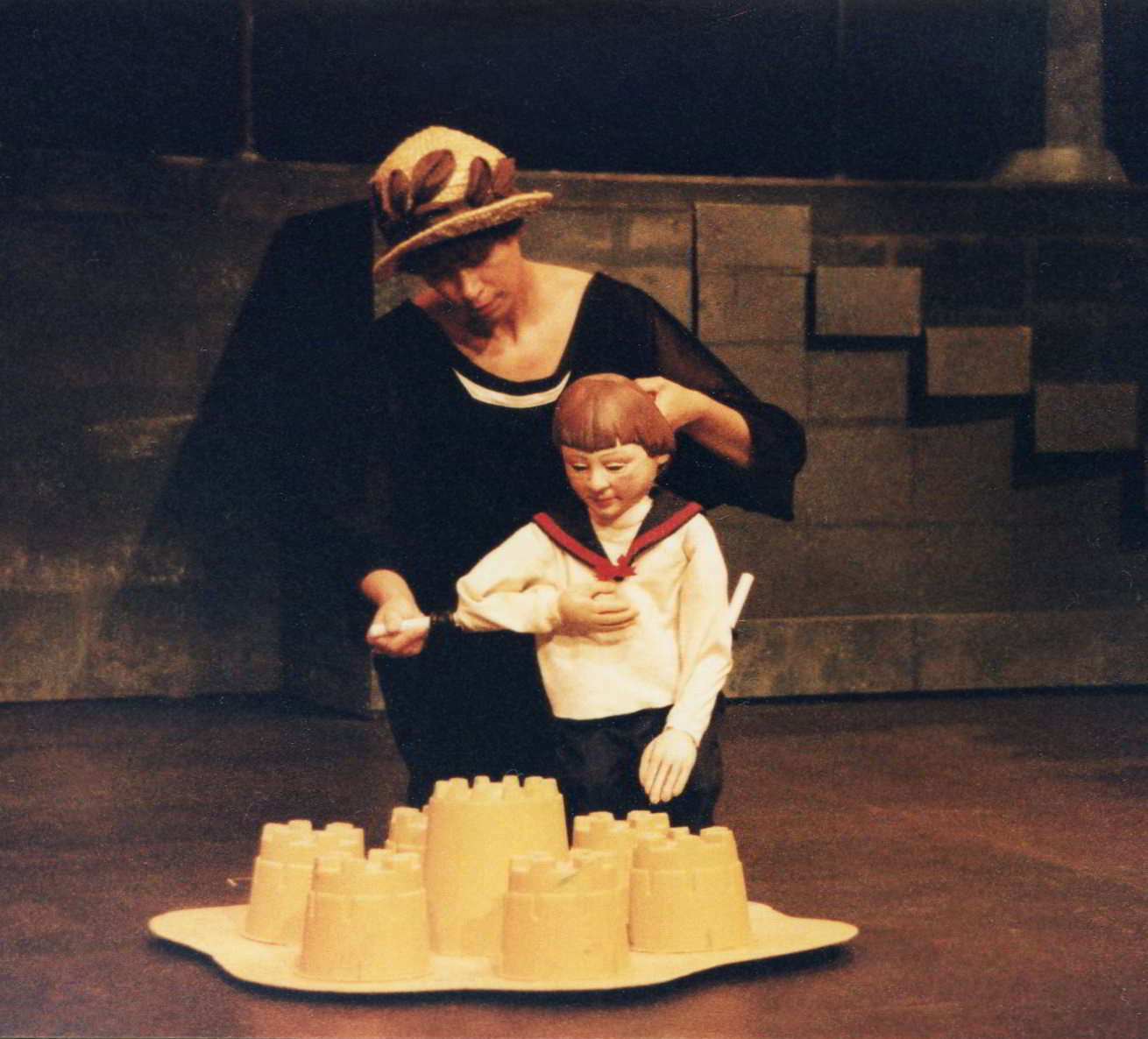 Actor as nanny helps puppet boy build sand castles