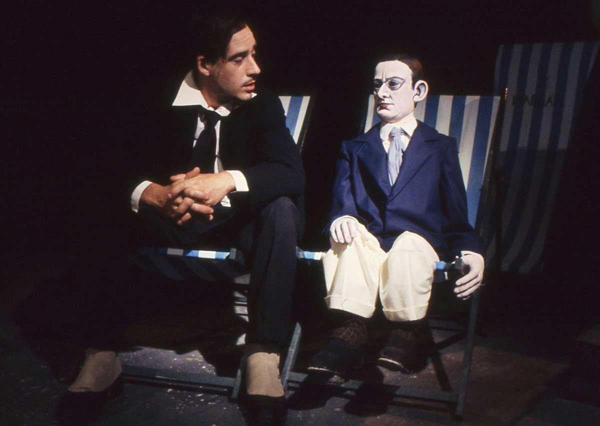 man and puppet man in conversation sitting on deckchairs
