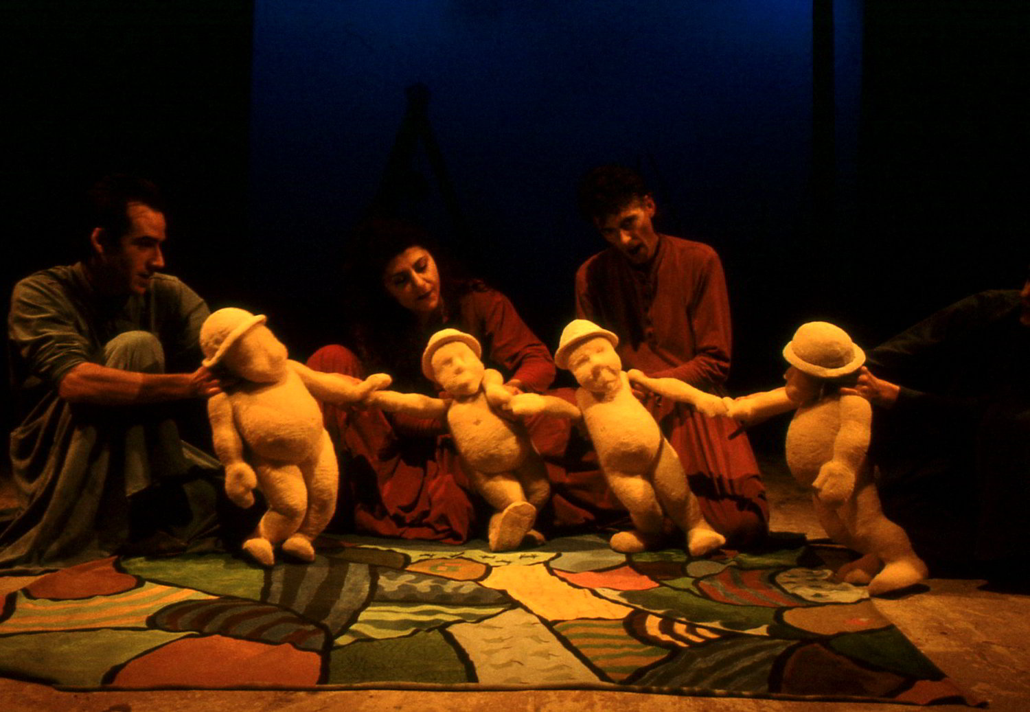 3 puppeteers with 4 foam sculpted figures wearing hats on patchwork floorcloth