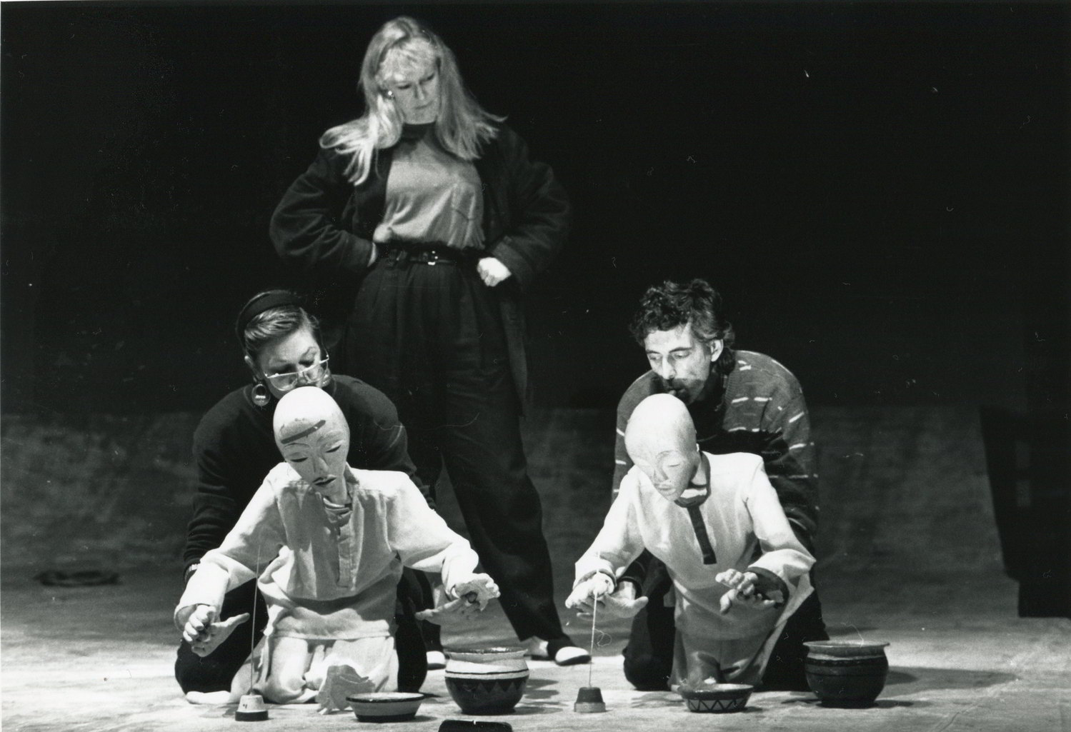 black & white photo of director standing behind 2 puppeteers & their puppets rehearsing a dining scene