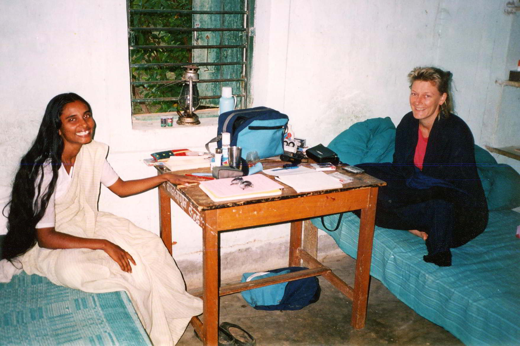 Australian woman and Indian woman working at a table in a small bedroom in India