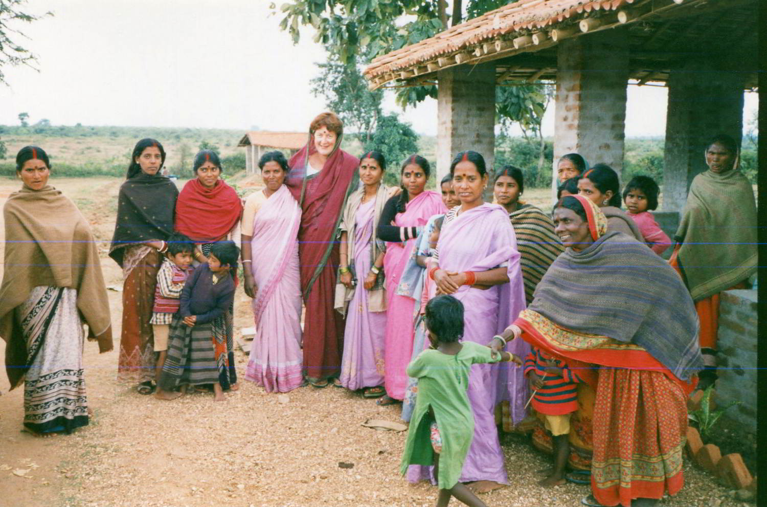 group portrait of local villagers dressed in their best with costumed Australian visitor in the middle