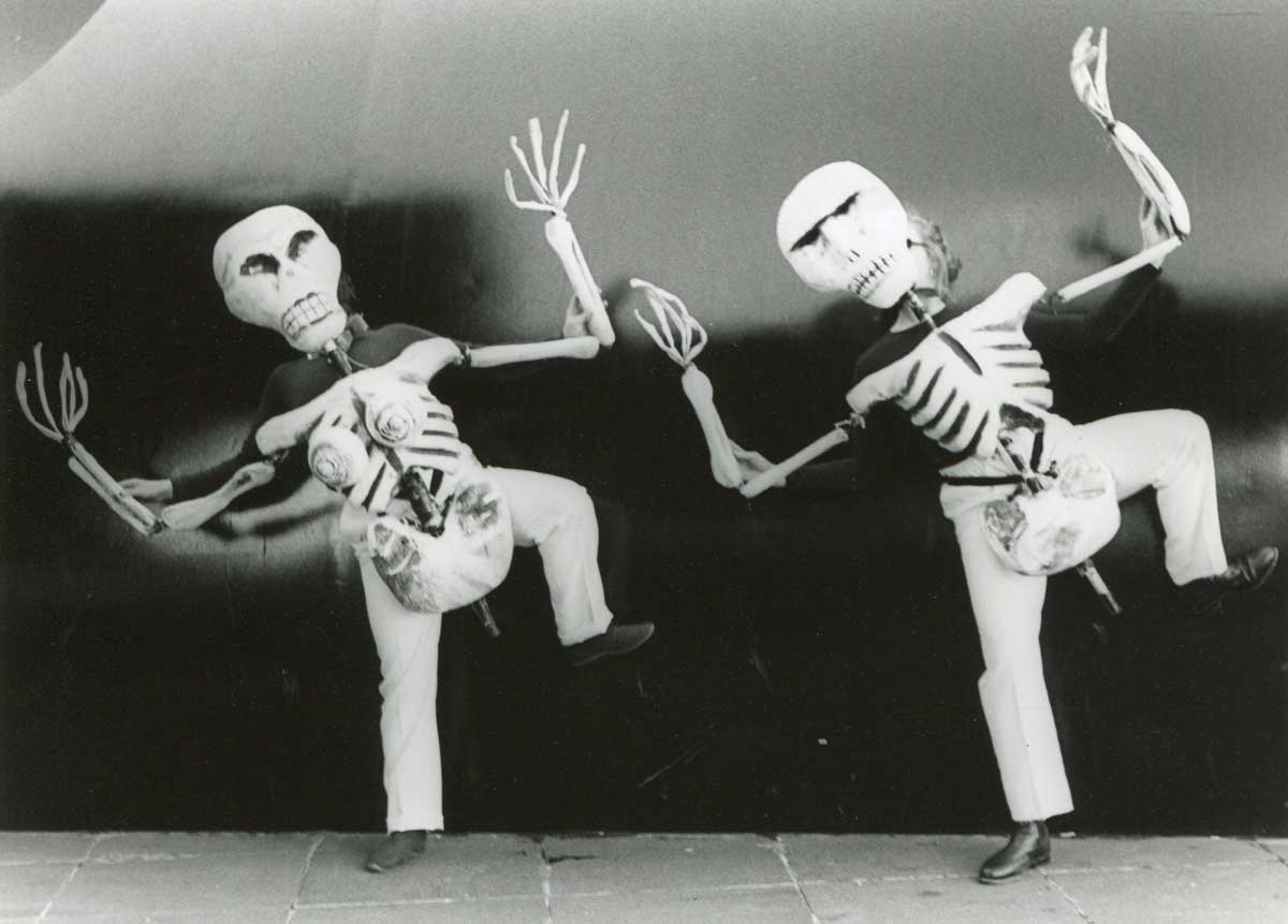 black and white picture of 2 skeleton body puppets dancing against an outdoor stone wall