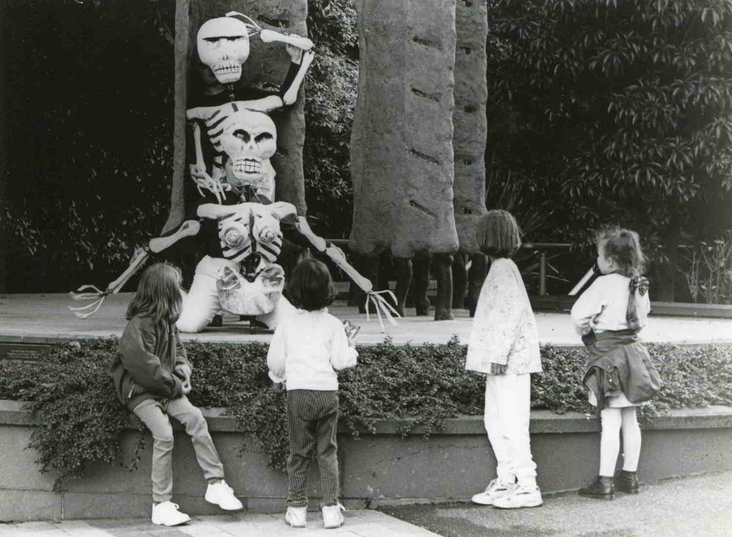 4 children looking at 2 large skeleton puppets leaning at the base of a stone plinth