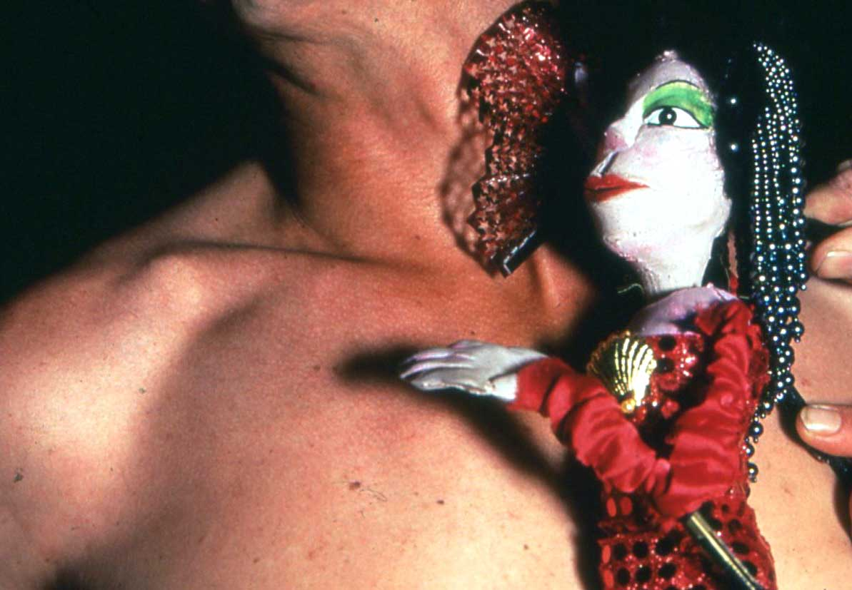 bare-chested man holding a sequinned lady puppet