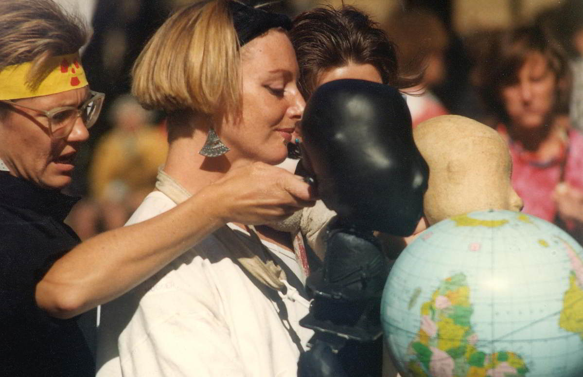 women with abstract puppet figures 1 black and 1 white sharing the carrying of a world globe