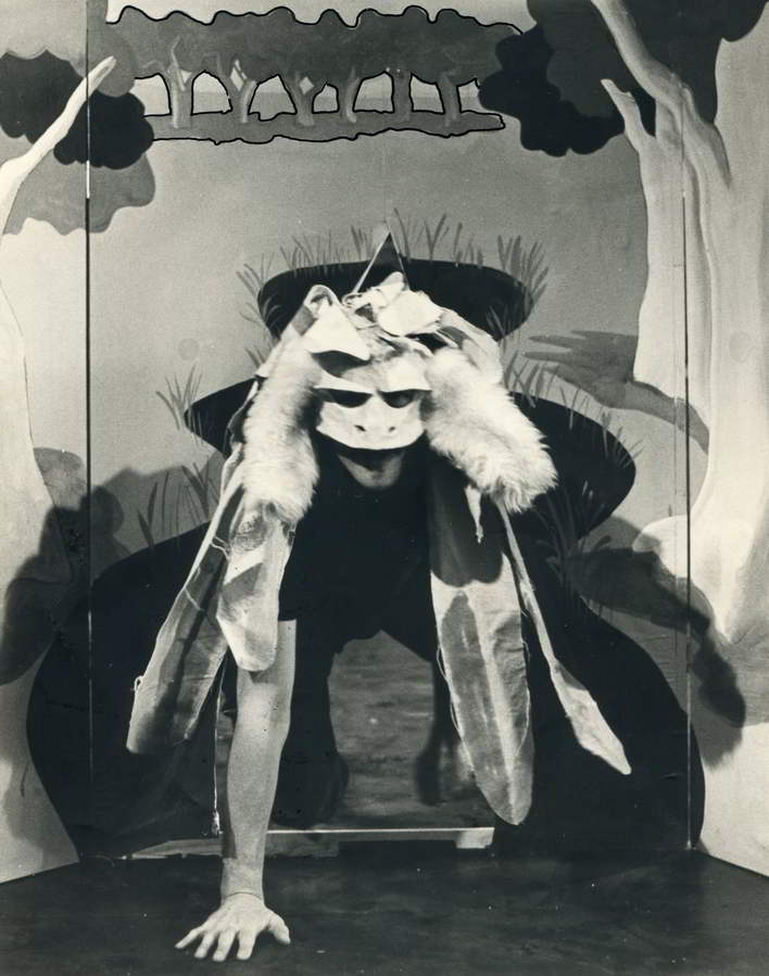 The Bunyip of Berkeley's Creek Handspan Theatre actor in feathered and furred bunyip mask and costume emerging from painted backdrop waterhole