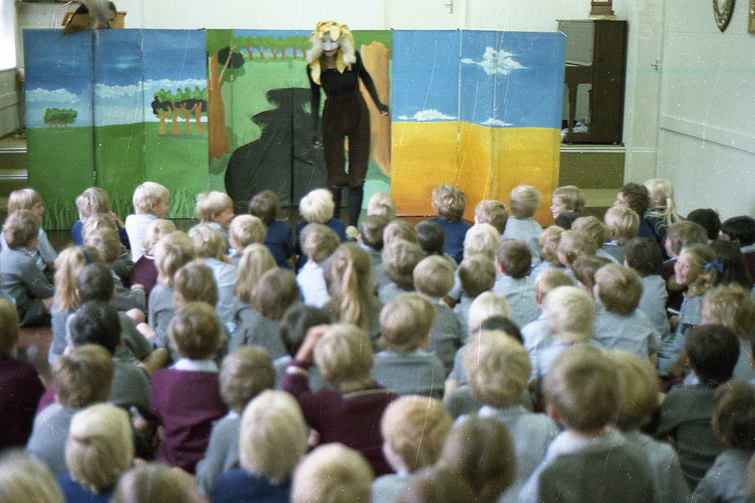 The Bunyip of Berkeley's Creek, Handspan Theatre Actor masked actor in front of stage flats painted with simple landscape, speaking to large group of children in classroom