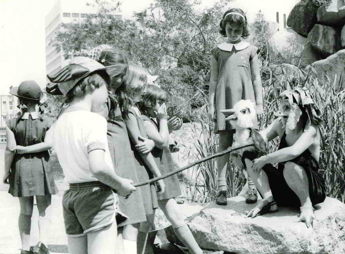 actor in bunyip costume sitting on a rock entertaining children with puppet kookaburra