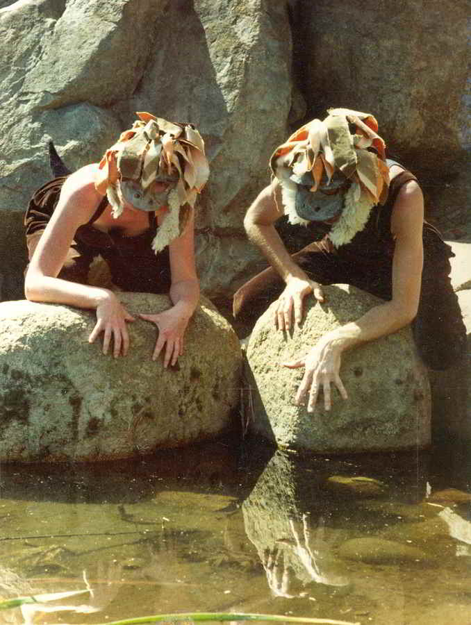 actors in bunyip masks and costumes on a rock looking at their reflections in water