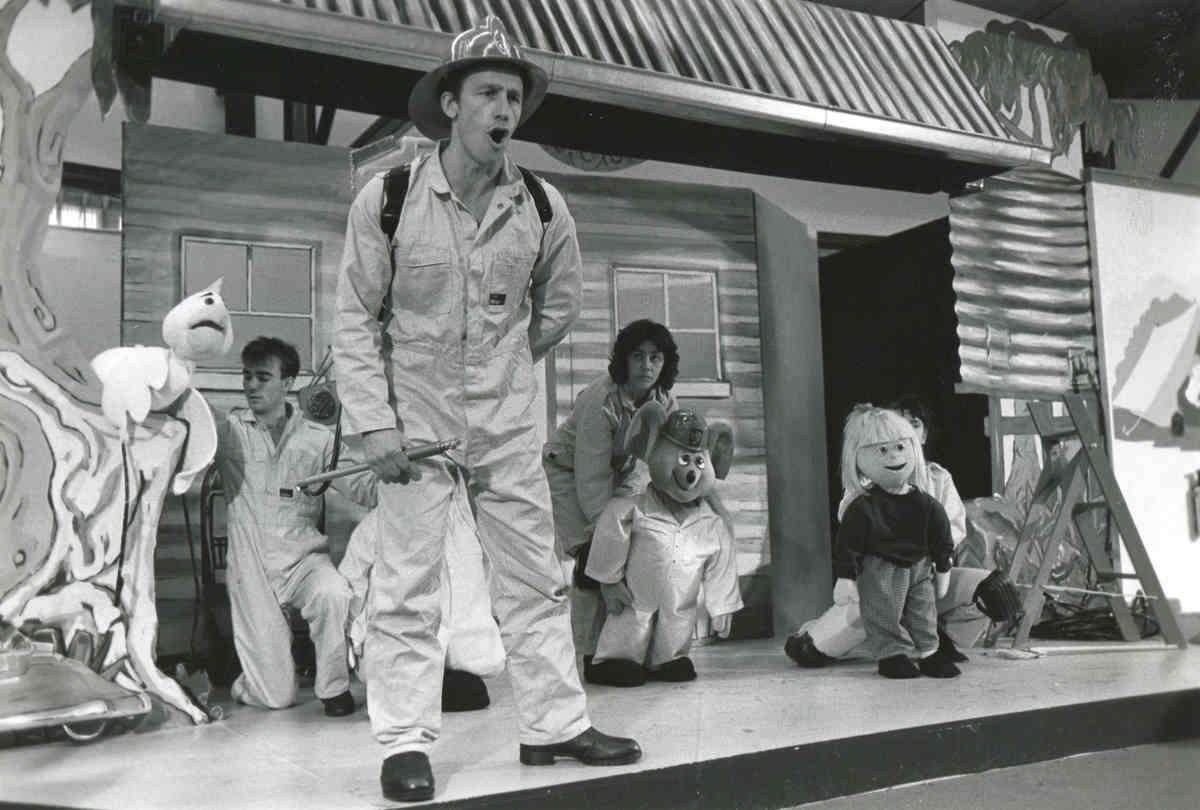 Handspan Theatre Captain Koala 3 people onstage with puppets and man in fire-fighter costume standing stage front, singing