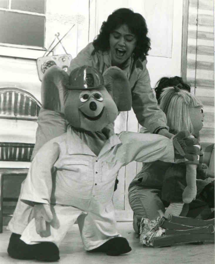 Handspan Theatre Captain Koala woman singing with large koala puppet in fire-fighter costume