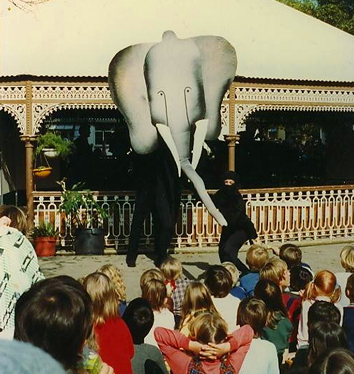 elephant head puppet in front of rotunda with children watching