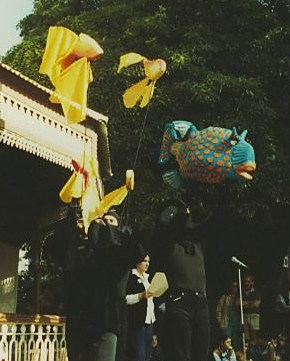 2 people outside parkrotunda holding aloft large brightly-coloured fabric goldfish on sticks