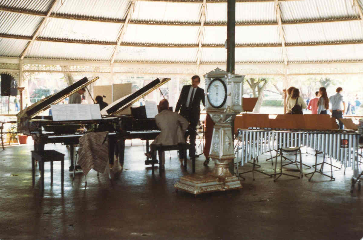 musicians inside park rotunda with 2 pianos and percussion section, old elaborate weighing machine in forground