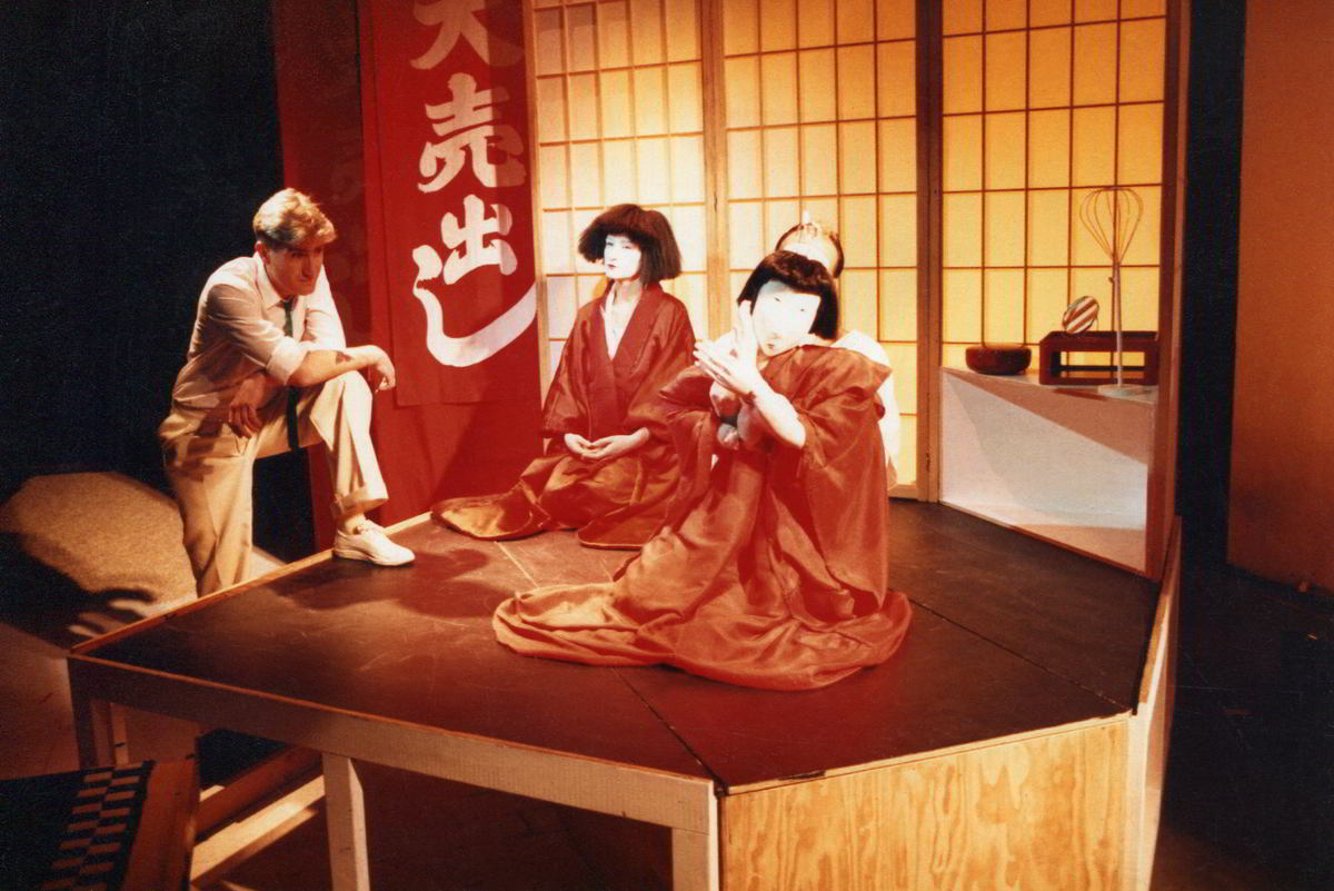 male actor in white leaning towards a woman and her puppet alter ego in red in Japanese tatami-room style setting
