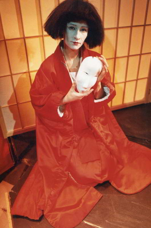 female actor in red kimono with white mask