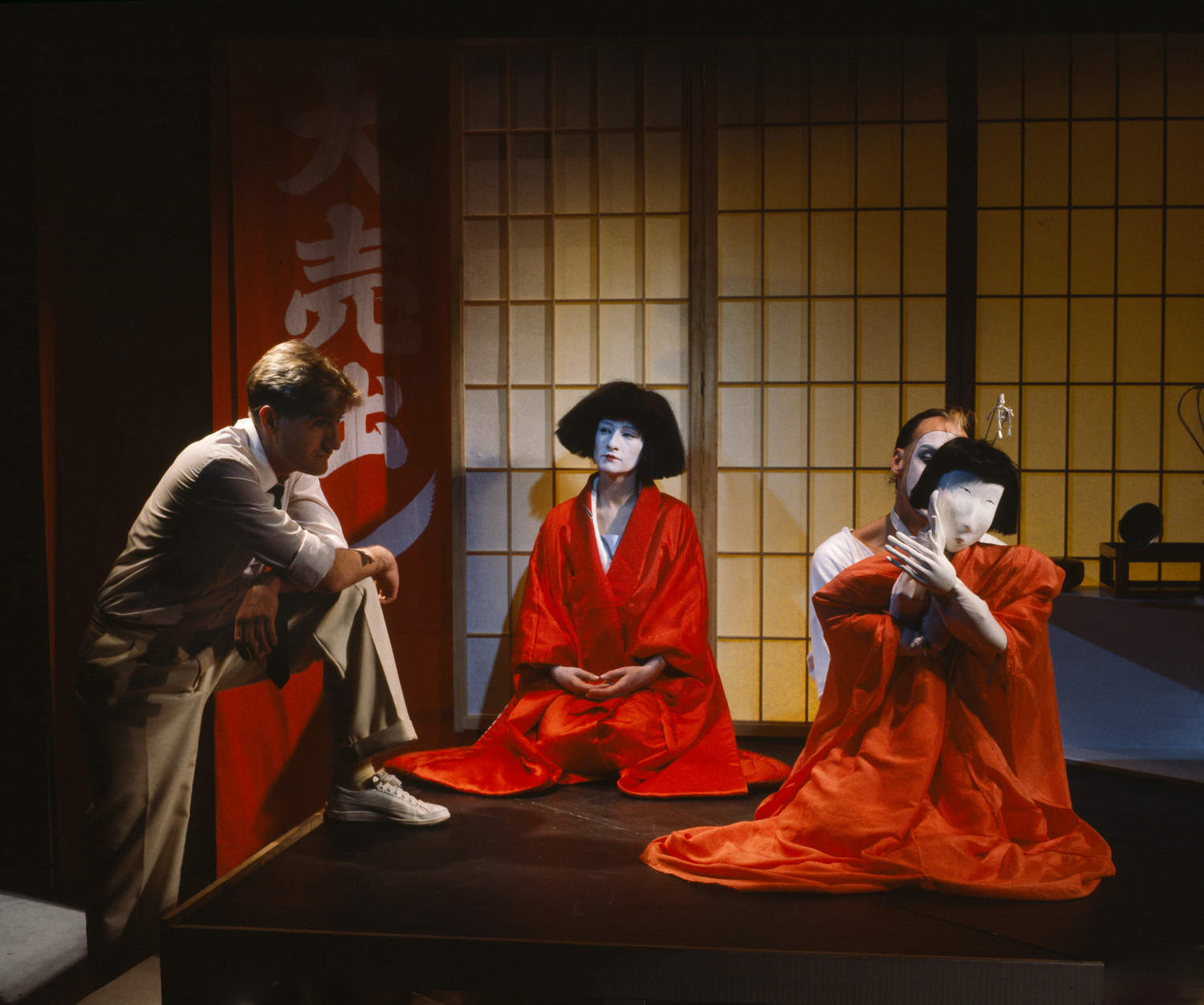 Man, woman and puppeteer with life-size puppet, in Japanese-style room.