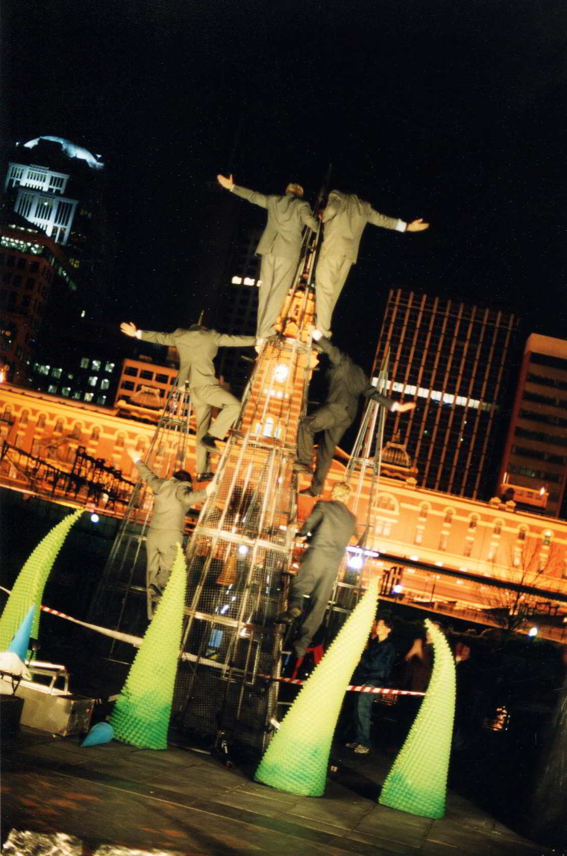 back view of acrobats at night in a 3-high tower in front of city buildings