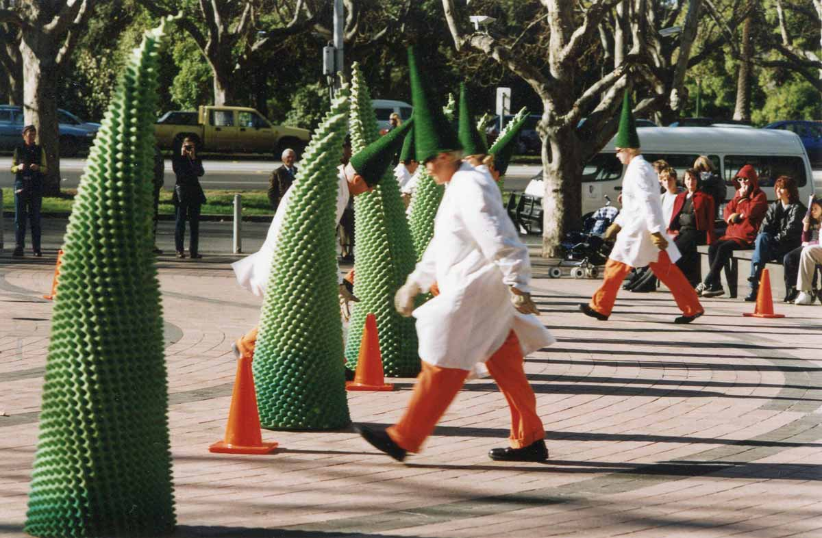 clowns in white lab coats with conical hats performing with green rubber cones