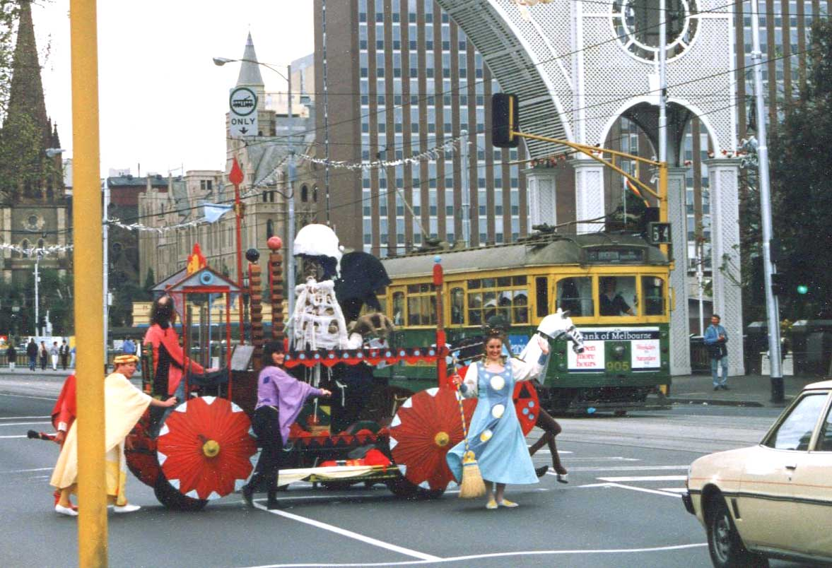 colourful float with red parasol wheels pushed by costumed performers across a city street