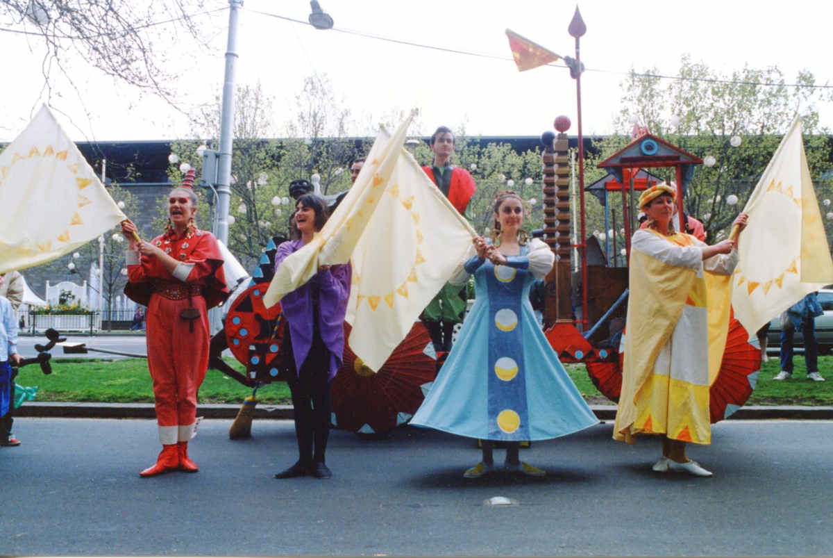 costumed performers in front of float waving large colourful flags on city street outside National Gallery of Victoria
