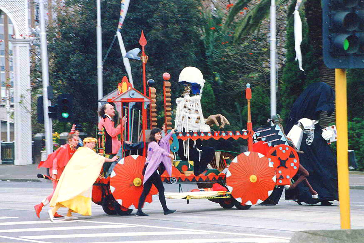 colourful float with red parasol wheels pushed by costumed performers actoss city intersection