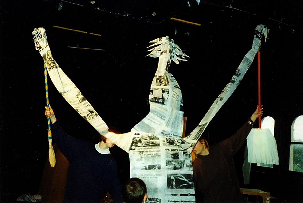 Handspan Theatre Daze of Our Lives Newspaper rod puppet with small head of spiky hair and pointy nose and very long arms pointing upwards