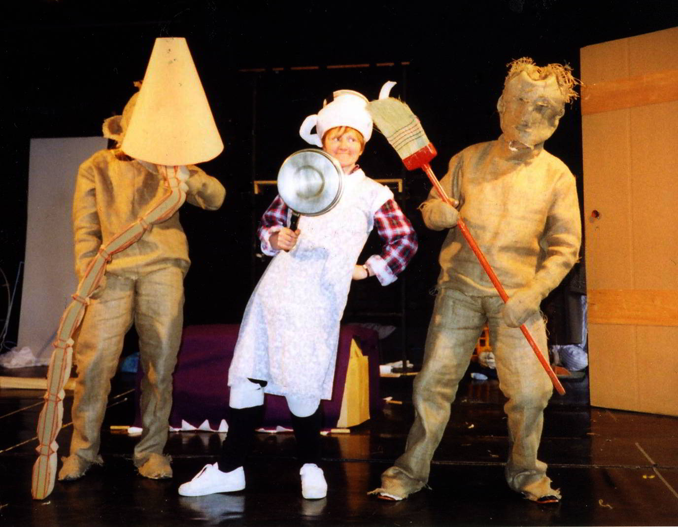 hessian bag figures holding a lampshade (L) and a broom (R) in dance rehearsal with woman dressed in white holding a saucepan