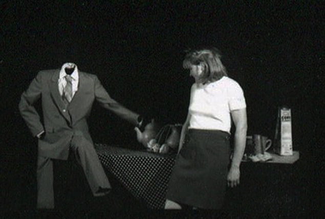 Handspan Theatre Daze of Our Lives headless suited man puppet perched on breakfast table in conversation with a woman