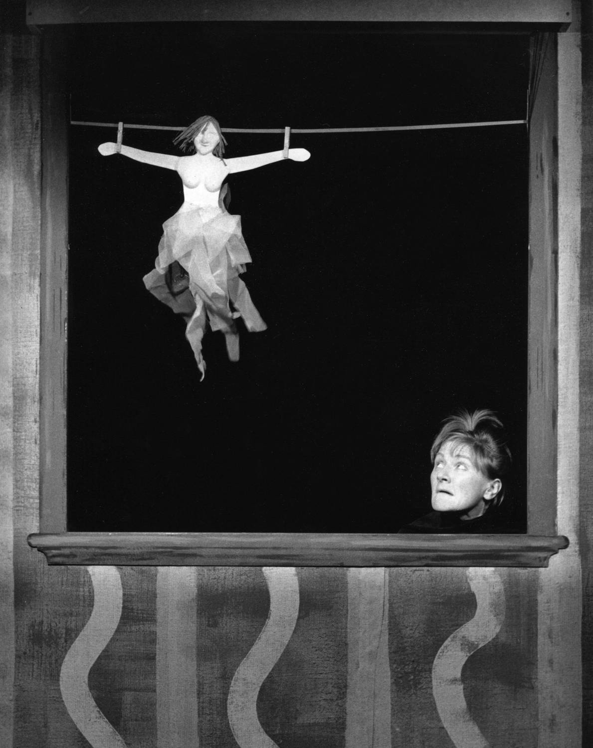 woman's face looking up front the bottom of a booth opening at a fairy figure hanging in the air