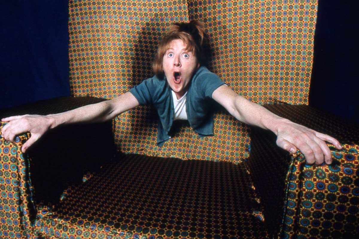 woman disappearing into the back of an armchair