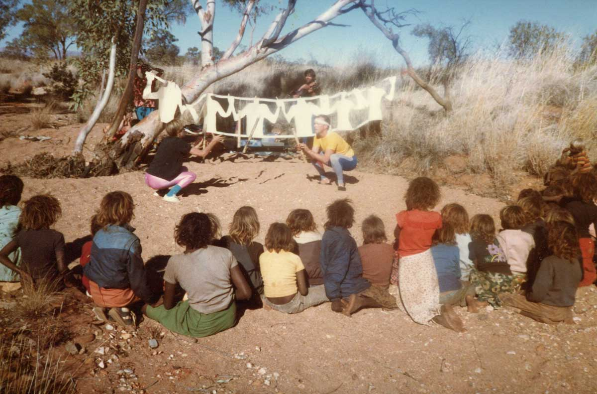 performers squatting in sandy riverbed with backgrop of cut out white figures and audience of Aboriginal children from behind