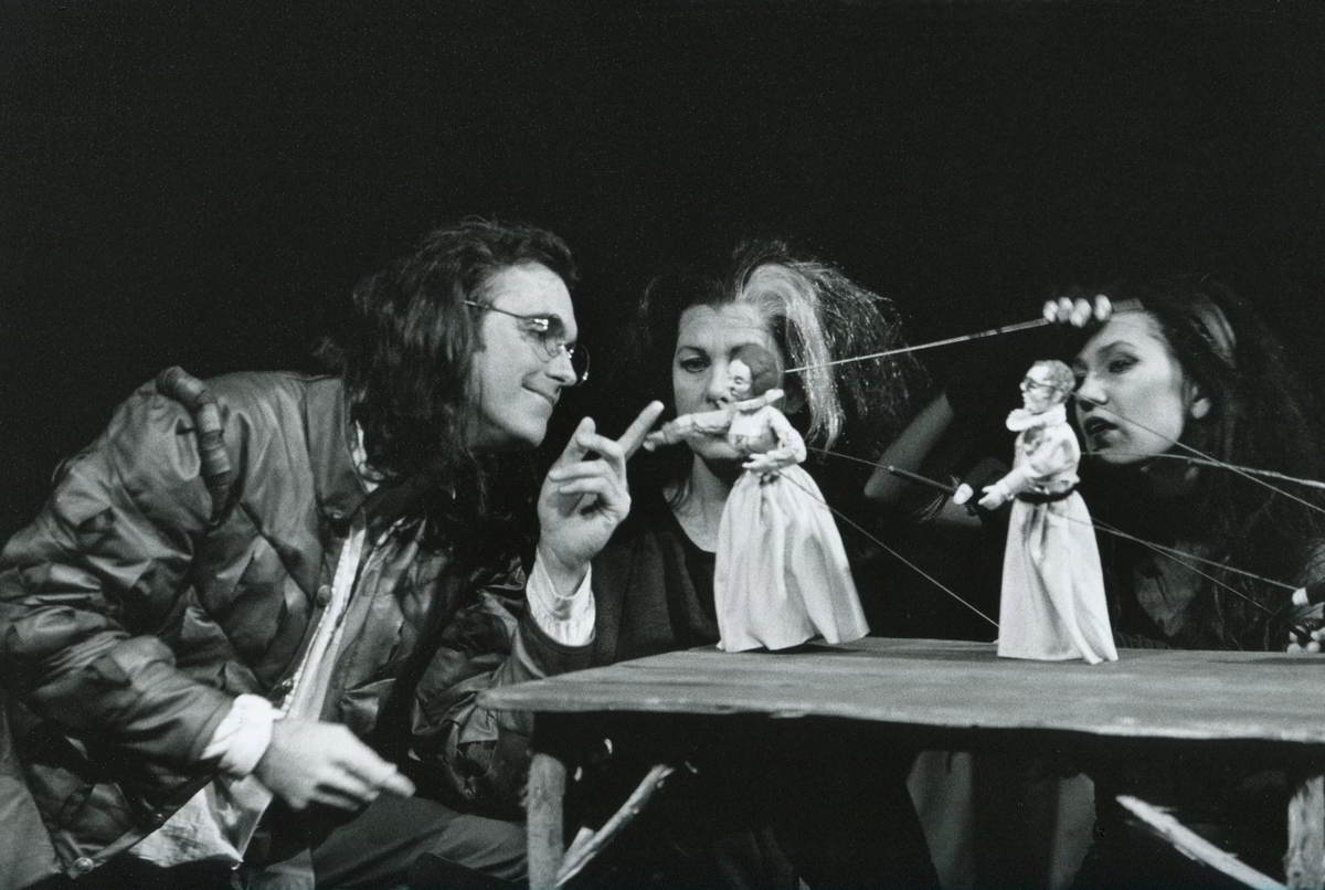 Gulliver a seated actor in conversation with two rod puppet women with visible operators