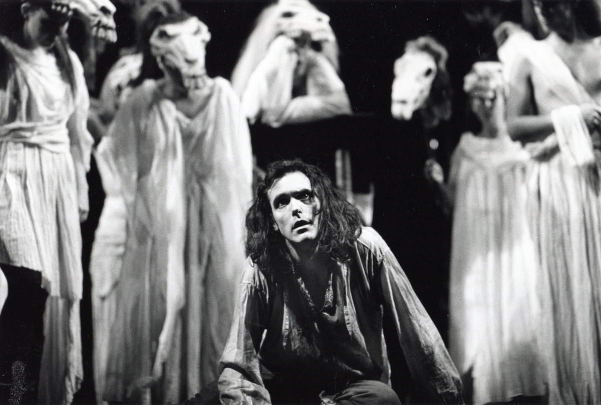 man on his knees in anguish surrounded by horse headed actors wearing long draperies