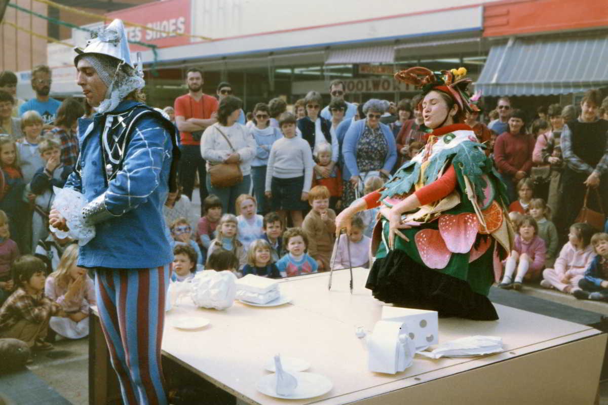 table set up in a crowded street with white food objects and performers dressed as king and prince