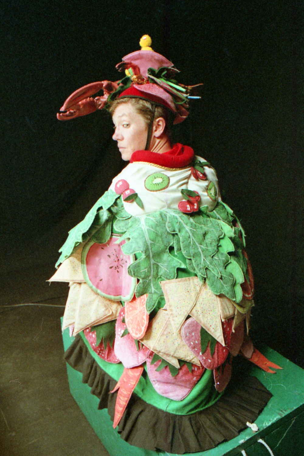 Handspan Theatre Guts costumed actors squatting in embroidered cloak of green leaves and pink vegetables with a lobster helmet