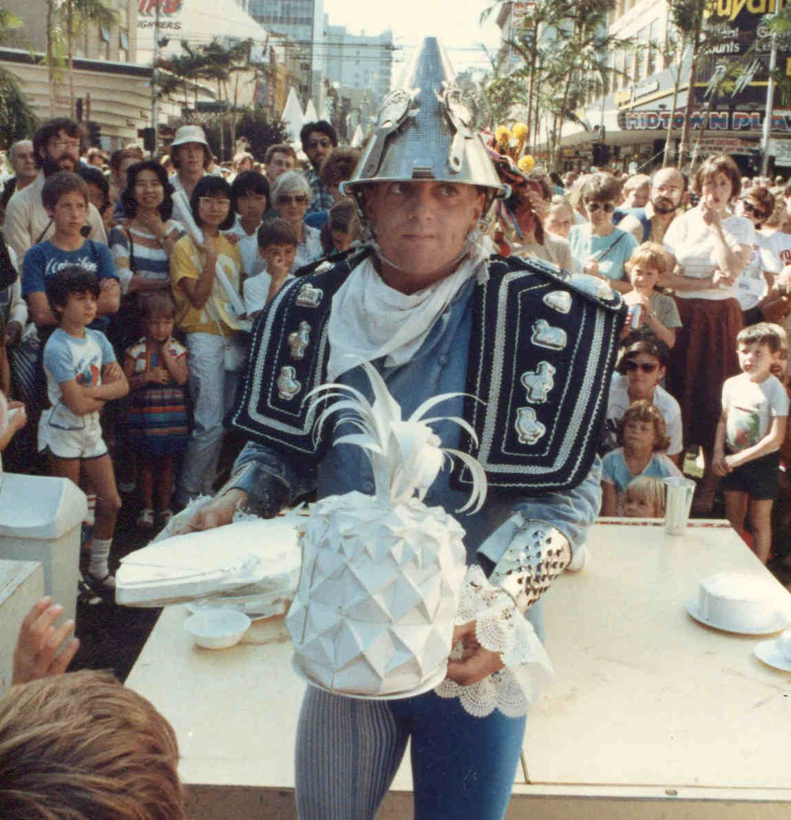 Handspan Theatre Guts costumed actor in blue with colander helmet holding white cardboard pineapple