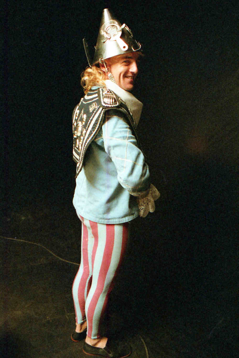 Handspan Theatre Guts costumed actor wearing blue and silver jacket, striped blue and purple tights and silver colander helmet