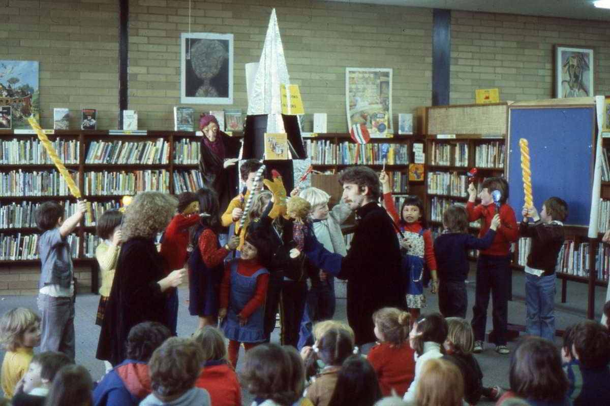 performance in a library with witch in rear and puppeteers amongst a crowd of children