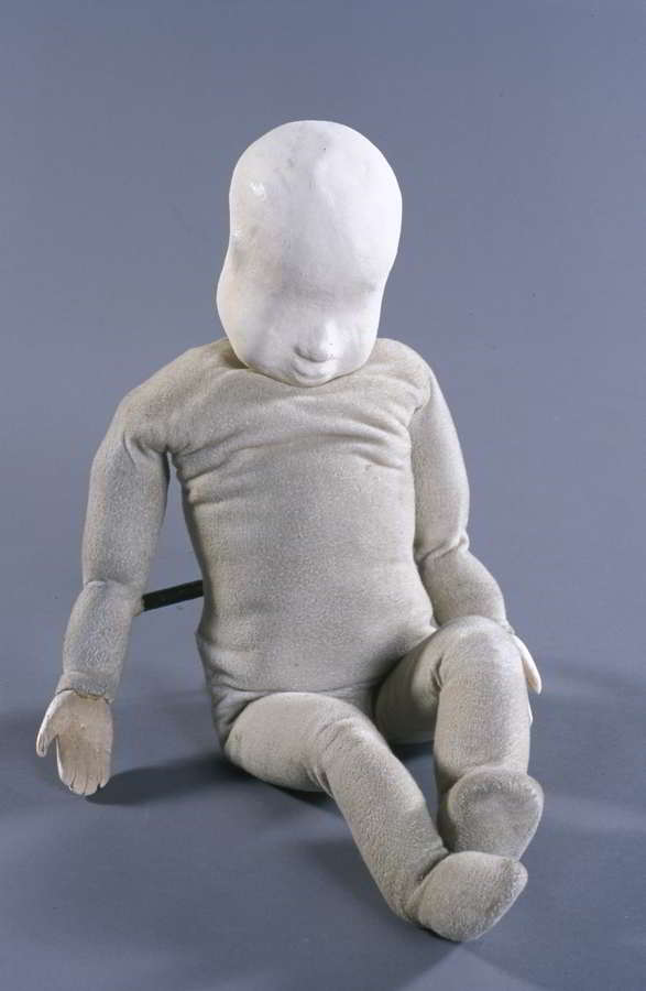 white baby puppet with featureless face seated