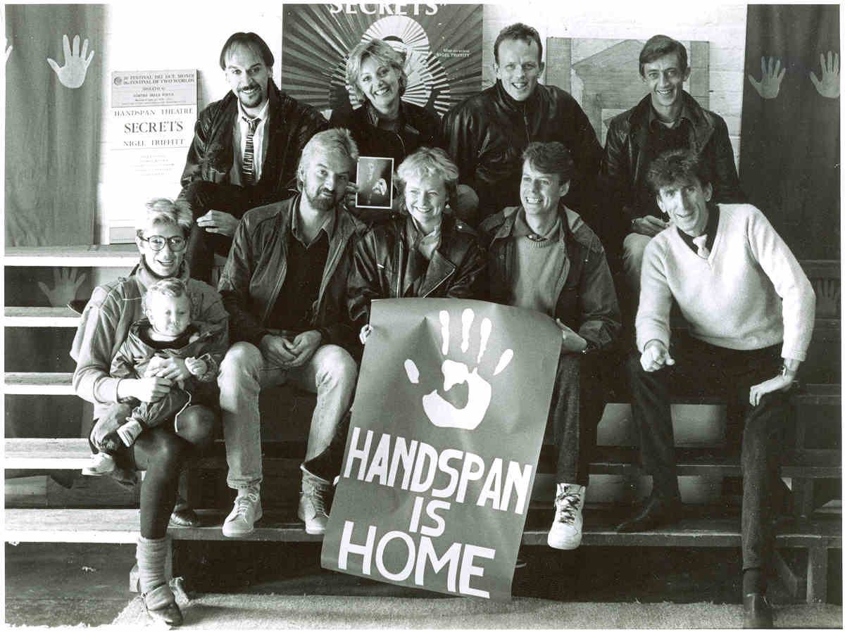 Handspan At Home people posed on bleachers with poster saying Handspan is Home