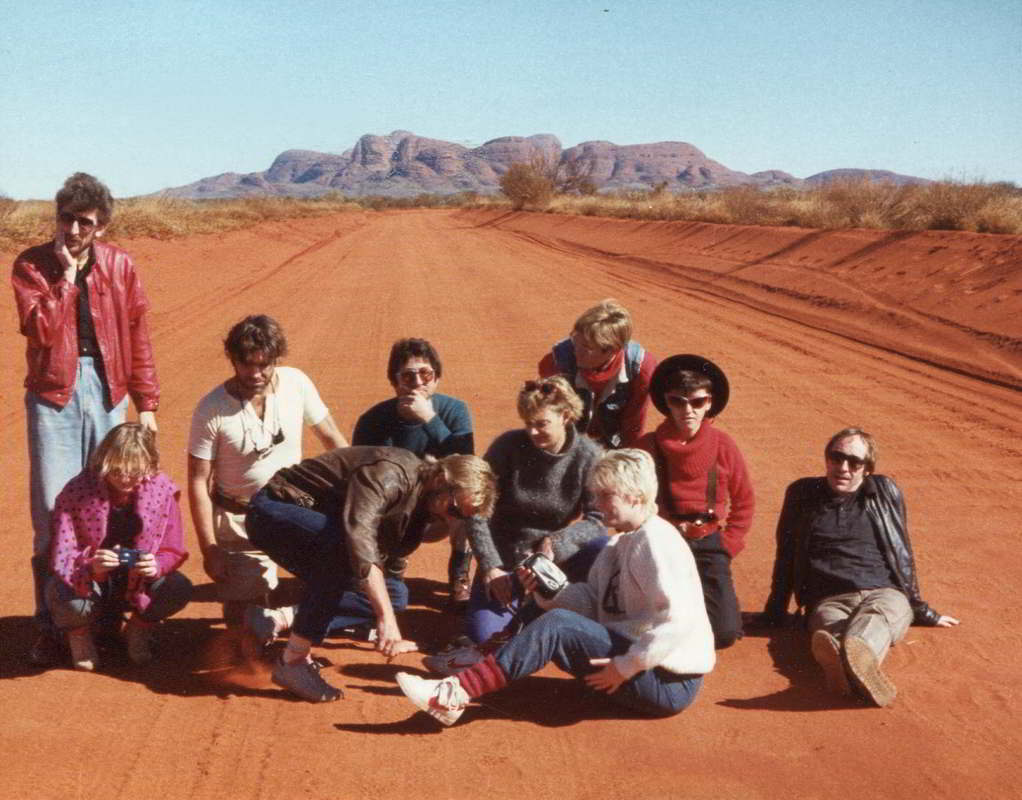 Handspan On the Road people sitting on a red desert road