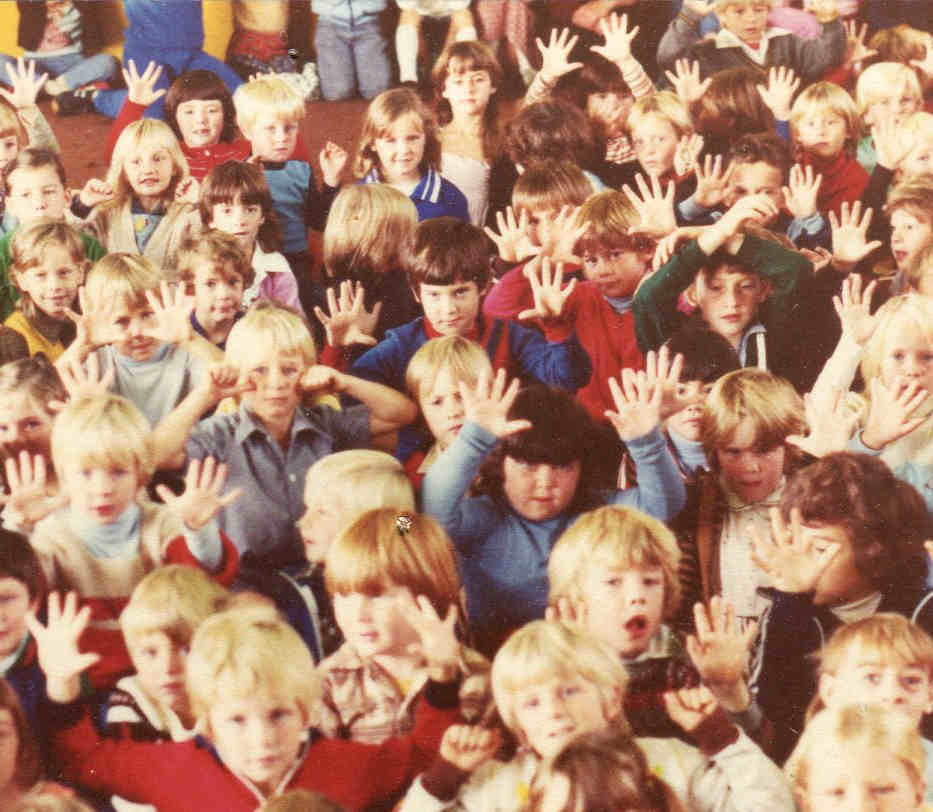 Handspan Theatre audience close-up of large group of children holding up their hands with palms facing camera