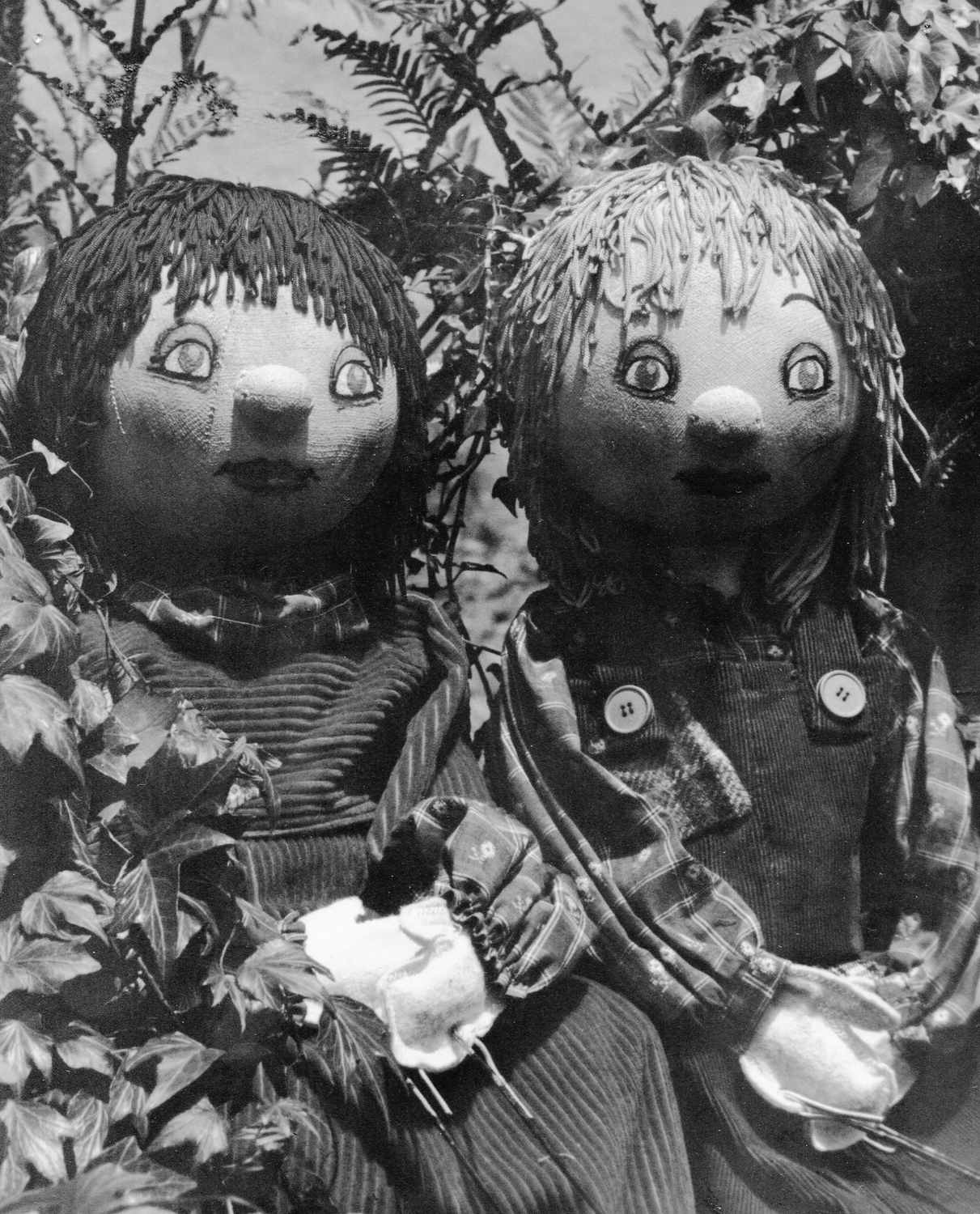 black and white picture of puppets in amongst foliage