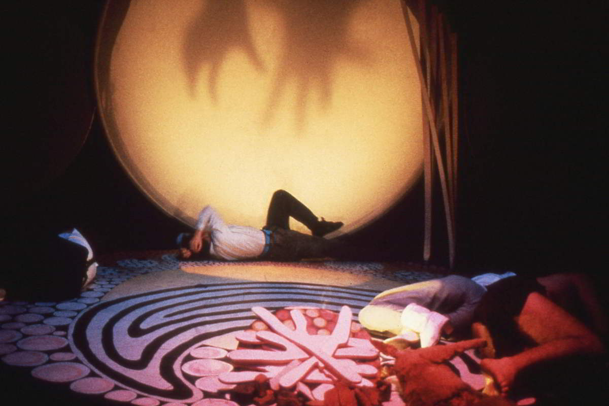 Handspan Theatre The Haunted scrim circle with stars and woman rolling on dot painted floor cloth crying