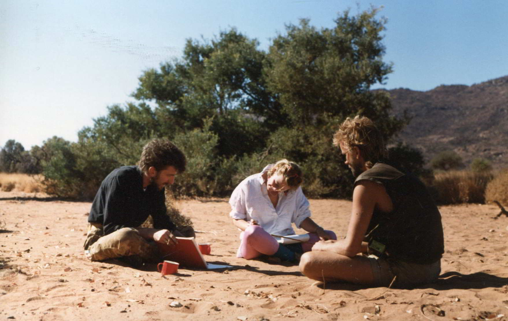 2 men and a woman at a working meeting sitting on desert ground